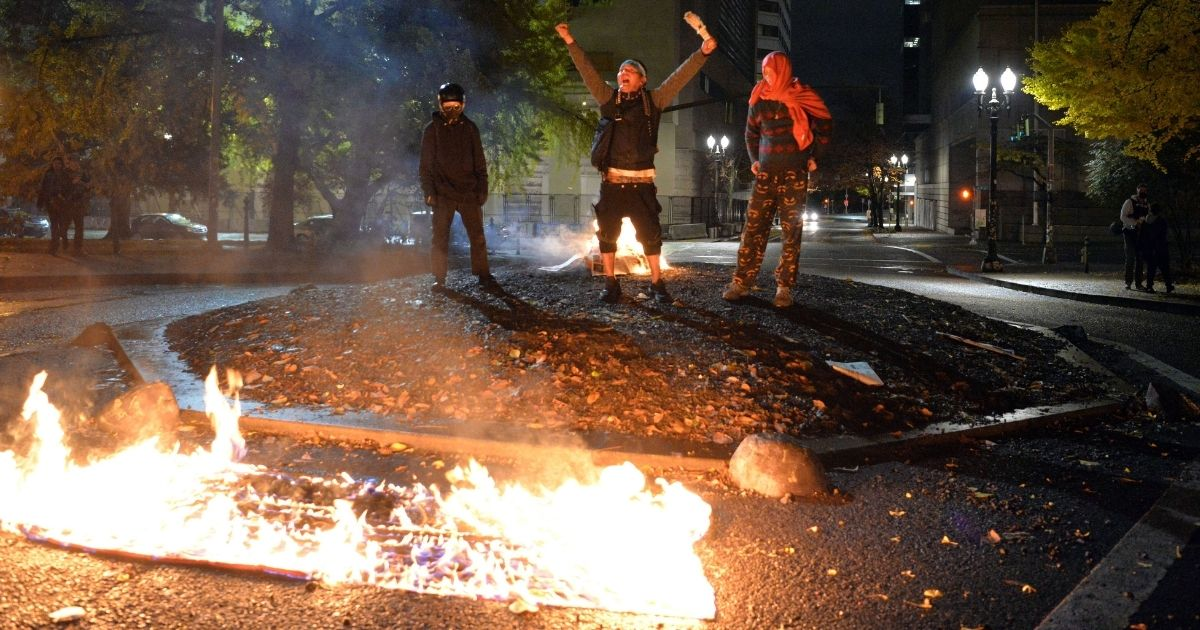 Protesters burn the American flag outside the Mark O. Hatfield United States Courthouse in Portland, Oregon, on Nov. 4, 2020.