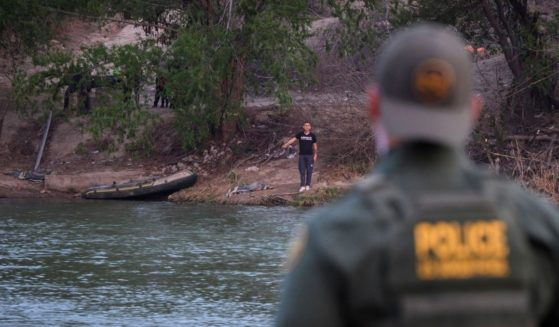 """A Border Patrol agent stands opposite a man believed to be a """"coyote"""" on the banks of the Mexican side of the Rio Grande river in the U.S. border city of Roma on Mach 27, 2021."""
