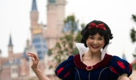 An actress dressed as Snow White poses in front of the Enchanted Storybook Castle at Shanghai Disney Resort in Shanghai on June 15, 2016.