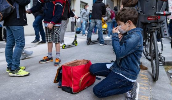 A boy adjusts his face mask before entering primary school in Paris April 26.